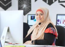A woman in a hijab sitting at a mac computer with books and magazines nearby